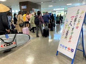 空の玄関口・奄美空港。到着ロビーにはメッセージ看板が設置され、来島者に新型コロナ感染防止のためのマスク着用を呼び掛けている=18日、奄美市笠利町