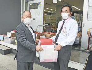 「ささえ愛クーポン券」を古仁屋郵便局に届けた鎌田町長(左)=23日、瀬戸内町古仁屋