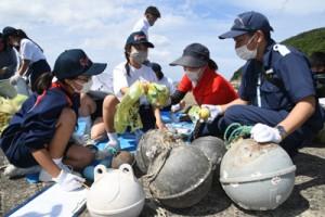 拾い集めた漂着ごみを分類する生徒ら=28日、龍郷町嘉渡