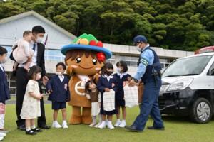 警察官から防犯グッズを手渡される新入生児童=6日、宇検村の田検小学校