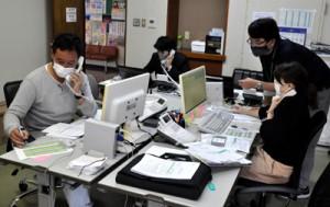 電話対応に追われる専任のスタッフら=19日午前9時、龍郷町役場