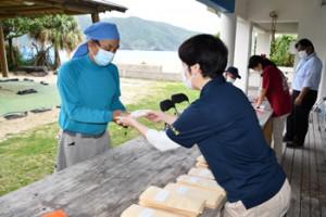 役場職員から地域商品券を受け取る住民(左)=26日、大和村国直