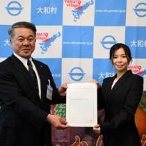 伊集院村長(左)から委嘱状を受け取った地域おこし協力隊の中野さん=14日、大和村役場
