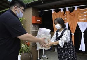 町職員から弁当容器を受け取る飲食店事業者=3月31日、瀬戸内町古仁屋