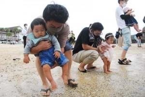 無病息災を祈って赤ちゃんの足を海水に浸す家族ら=14日、奄美市笠利町の用安海岸