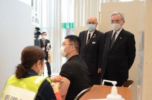 奄美ワクチンセンター開設初日、接種状況を視察する(右から)朝山市長、竹田町長=19日、奄美市名瀬