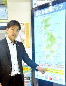デジタルサイネージの操作法を説明する県徳之島事務所職員=13日、徳之島空港