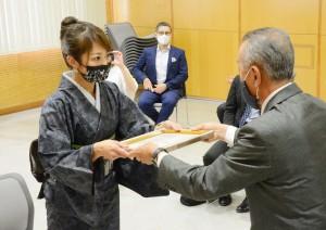 奄美観光大使の委嘱状を受け取る緒方さん(左)=8日、奄美市名瀬