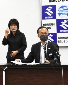記者会見で県の感染状況などについて述べる谷口くらし保健福祉部長(右)=1日、鹿児島市の県庁