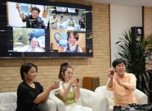 画面上の禎さん、あずまさん、安田さんと乾杯する(左から)新成人の祷さん、眞形さん=2日、徳之島町亀津