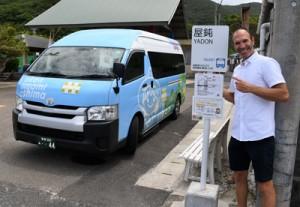 宇検村を運行するラッピングバスと停留所の新しい標識をデザインしたマットさん=4日、同村屋鈍