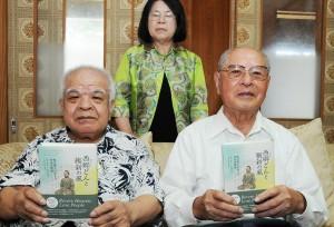 著書「西郷どんと維新の風」を手に、出版を報告する(前列右から)竿田富夫さん、豊さん兄弟=2日、和泊町