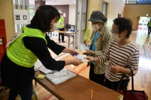 2回目のワクチン接種を終え、役場職員から接種済証を受け取る高齢者=9日、大和村体育館