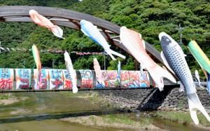 新型コロナウイルスの収束を願い、大和川に設置されたこいのぼりと横断幕=4日、大和村大和浜