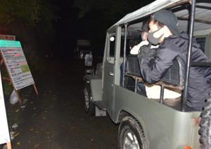 看板で野生生物の観察ルールなどを確認するナイトツアー客=4月29日午後8時ごろ、奄美市住用町